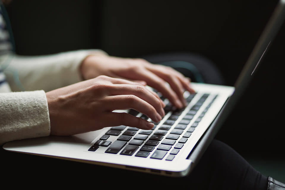 Closeup of woman typing on her laptop