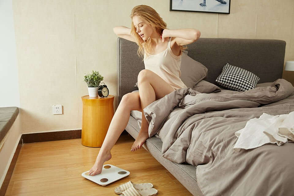 Woman waking up and taking her weight