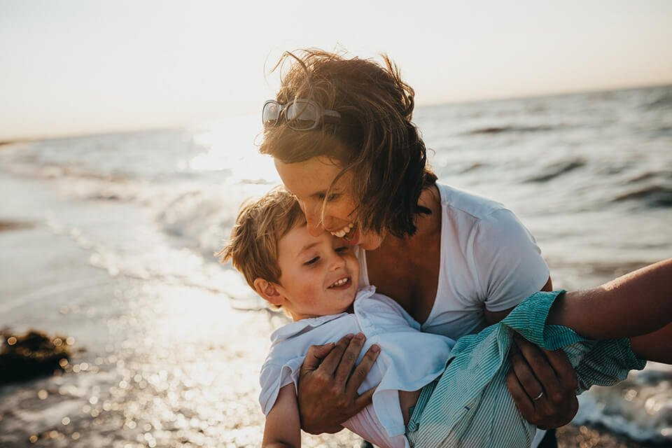 Woman smiling and carry her child on the beach.