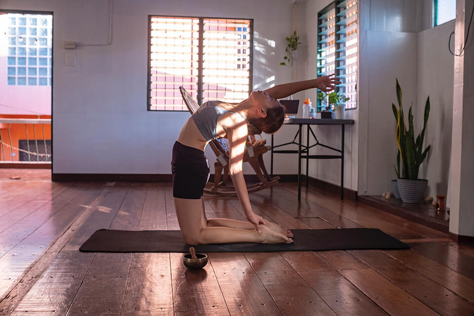 Woman doing yoga inside her home